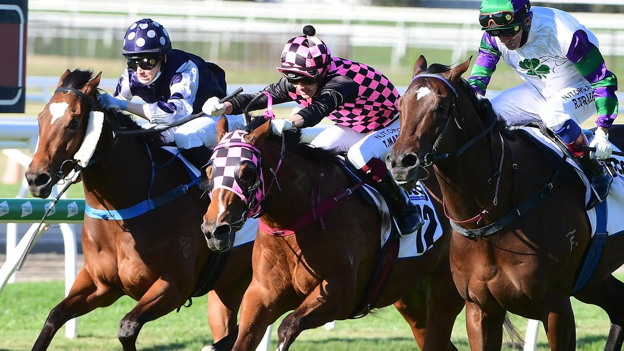 Startantes (pink and black) and jockey Taylor Marshall thread through the gap to beat Alpine Edge (right) and Glorious Ruby at Doomben. Picture: Trackside Photography