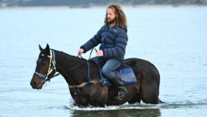 Trainer Ciaron Maher riding Sir Dragonet at the beach. Picture: Getty Images