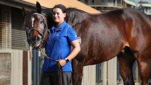 Trekking with stablehand Lizzy Grima ahead of the Doomben 10,000. Picture: Liam Kidston